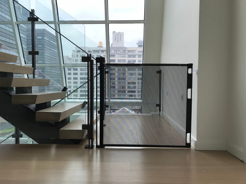 Black stair gate on glass railing